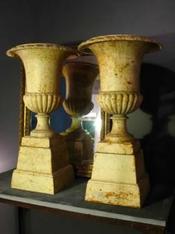 PAIR OF FRENCH PAINTED CAST IRON URNS ON PLINTHS